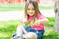 Little girl  outdoors shows gestures Royalty Free Stock Images