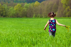 Little girl outdoors on spring field Royalty Free Stock Photos