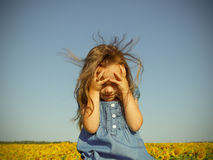 Little girl over a field of sunflowers Royalty Free Stock Photos