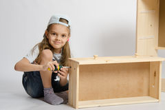 Little girl in overalls collector collects furniture drawer of the dresser Royalty Free Stock Images