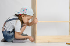 Little girl in overalls collector furniture screw spins Stock Photo