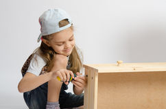 Little girl in overalls collector of furniture screws screwdriver screw Royalty Free Stock Photos