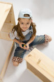 Little girl in overalls collector furniture spins screwdriver Stock Photos