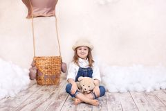 A little girl in overalls sits on the floor with a teddy bear on the background of a balloon and clouds. The little girl is dreami stock images