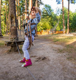 Little girl overcomes obstacles. Three-year girl the blonde with a personal fall arrest system obstacle in the rope town royalty free stock photos