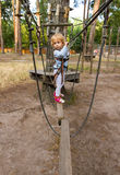 Little girl overcomes obstacles. Three-year girl the blonde with a personal fall arrest system obstacle in the rope town royalty free stock image