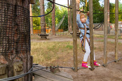 Little girl overcomes obstacles. Three-year girl the blonde with a personal fall arrest system obstacle in the rope town stock photo