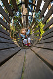 Little girl overcomes obstacles. Three-year girl the blonde with a personal fall arrest system obstacle in the rope town royalty free stock photography