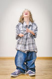 Little girl in oversized jeans and shirt. Royalty Free Stock Images