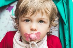 Little girl with a pacifier in her mouth. Lovely blonde girl royalty free stock image