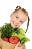 Little girl with a package of vegetables Royalty Free Stock Photography