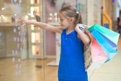 Little girl with packages in a large shopping Royalty Free Stock Images