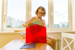 Little girl is packing his school backpack sitting on the desk. School, education, knowledge and children. stock photos