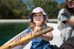 Little girl paddling in a boat. Four years old blonde girl with hat sitting in boat next to women mother, looking and smiling happy, paddling at park lake royalty free stock photos