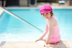 Little girl paddling her feet in a swimming pool. While looking back to the camera Royalty Free Stock Images