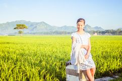 A Little Girl in the paddy field and smiling while holding her jacket stock photos
