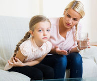 Little girl with pain in belly and worried mother indoors Stock Images