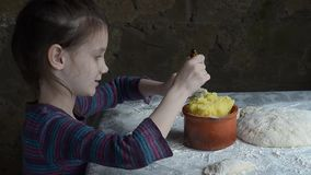 Little girl painstakingly sculpts cakes with potatoes. stock footage