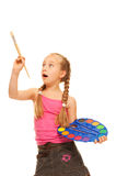 Little girl with a paintbrush Stock Photos