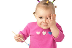 Little girl with paintbrush clasping hand to cheek Royalty Free Stock Images