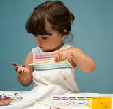 Little girl with paintbrush in her hand Stock Photo