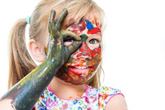 Little girl with painted face peeping through finger hole. Close up portrait of Little girl messed with color paint. Infant doing okay sign in front of eye royalty free stock photo