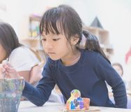 Little girl painting in art classroom. Little girl is painting in art classroom stock photos