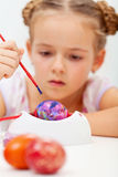 Little girl painting an artsy easter egg Royalty Free Stock Images