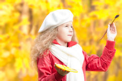 Little girl painting in autumn park. Stock Photos