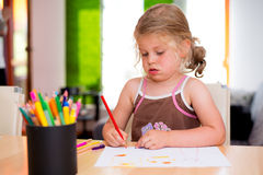 Little girl is painting Stock Images