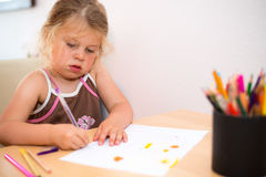 Little girl painting with colored pencil Stock Image