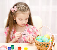Little girl painting colorful easter eggs Royalty Free Stock Photo