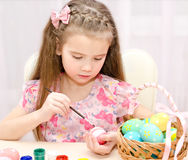 Little girl painting colorful easter eggs Royalty Free Stock Image
