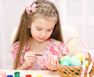 Little girl painting colorful easter eggs Royalty Free Stock Images