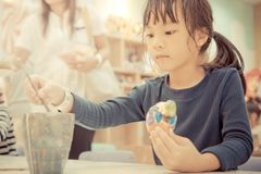 Little girl painting a doll in art classroom. Little girl is painting a doll in art classroom royalty free stock images