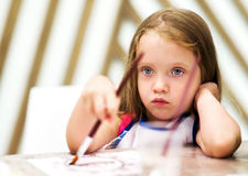 Little girl painting and dreaming Royalty Free Stock Image
