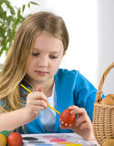 Little girl painting easter eggs Royalty Free Stock Images
