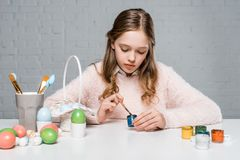 Little girl painting easter eggs at table. Beautiful little girl painting easter eggs at table Royalty Free Stock Images