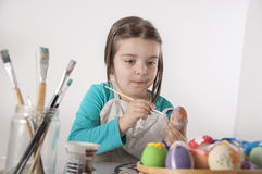 Little girl is painting eggs Stock Images