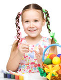 Little girl is painting eggs preparing for Easter Stock Photo