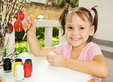 Little girl painting eggs Stock Images