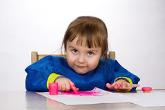 Little girl painting on paper Stock Photos