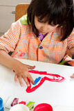 Little girl painting with fingers Stock Photos