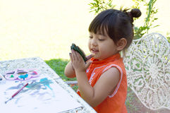 Little girl painting in garden at home stock images