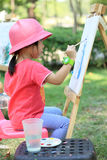 Little girl painting in the garden. Portrait of little girl painting in the garden Stock Photo