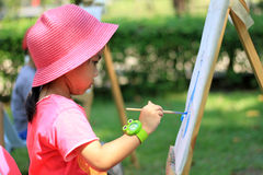 Little girl painting in the garden. Portrait little girl painting in the garden Royalty Free Stock Photography