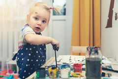 Little girl painting with gouache colors royalty free stock photo