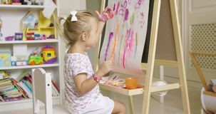 Little girl painting with her hand stock footage