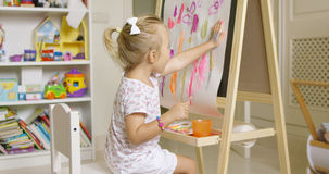 Little girl painting with her hand Stock Images