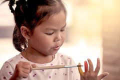 Little girl is painting her hand Stock Images